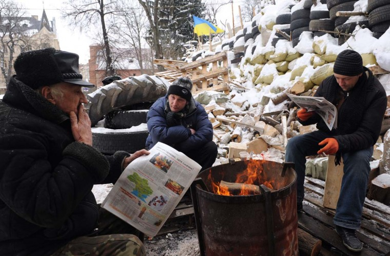 Anti-government protesters read newspaper as they sit by a barricade in Lviv, on January 27, 2014. Ukrainian police have arrested dozens of protesters who were trying to seize regional government headquarters in President Viktor Yanukovych's eastern heartland, local media reported on January 27. The reports said 37 protesters were arrested in Dnipropetrovsk, 30 in Zaporizhya, 12 in Cherkasy and 11 in Sumy following clashes with security forces that mirrored developments in the protest epicentre in Kiev. (Yuriy Dyachyshyn/AFP/Getty Images)