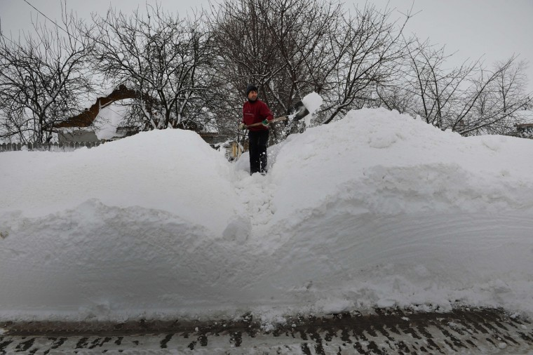 A man shovels snow in front of his home in Smeeni village about 100 kilometers east of Bucharest on January 28, 2013. A thick blanket of snow covered southern and eastern Romania causing the closure of three highways, cancelling twenty rail links and disruptions in air traffic. (Daniel Mihailescu/AFP/Getty Images)