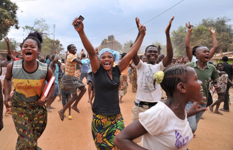 Residents of Bangui celebrate after former Seleka rebels were escorted out of Kasai military camp in Bangui to another camp outside the city on January 28, 2014. The UN Security Council will threaten sanctions on January 28 against the ringleaders of deadly turmoil in the Central African Republic and give a mandate to EU troops bolstering international forces there. The French-drafted resolution, expected to be adopted unanimously by the 15-nation council, also steps up pressure on interim President Catherine Samba Panza to restore order. (Issouf Sanogo/AFP/Getty Images)