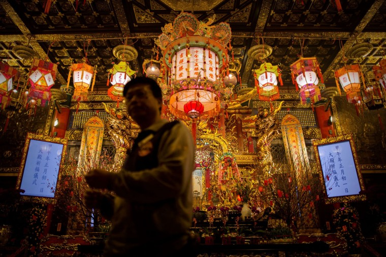 A man walks past an altar at the Wong Tai Sin Temple to welcome the Chinese New Year of the horse in Hong Kong on January 30, 2014. Tens of thousands of worshippers flocked to temples across to pray for good luck and fortune for the new year. (Philippe Lopez/AFP/Getty Images)