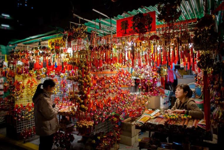 A woman shops outside a temple where worshippers burn incense and pray at the Wong Tai Sin Temple to welcome the Chinese New Year of the horse in Hong Kong on January 30, 2014. Tens of thousands of worshippers flocked to temples across to pray for good luck and fortune for the new year. (Philippe Lopez/AFP/Getty Images)