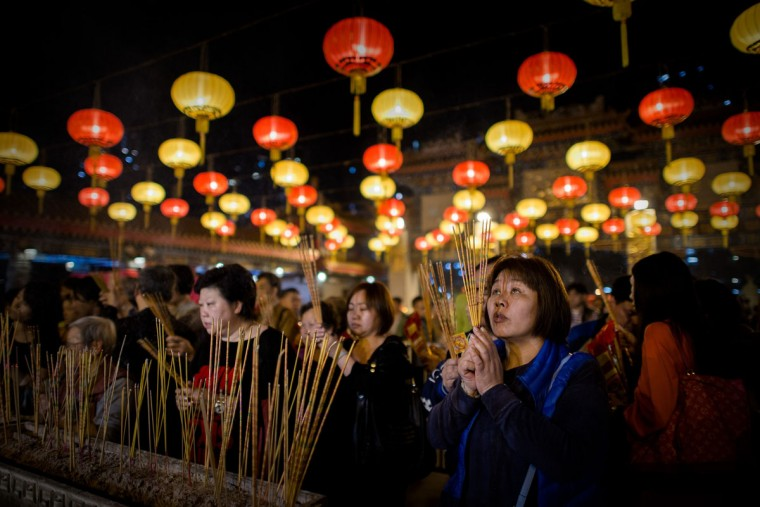 Worshippers burn incense and pray at the Wong Tai Sin Temple to welcome the Chinese New Year of the horse in Hong Kong on January 30, 2014. Tens of thousands of worshippers flocked to temples across to pray for good luck and fortune for the new year. (Philippe Lopez/AFP/Getty Images)
