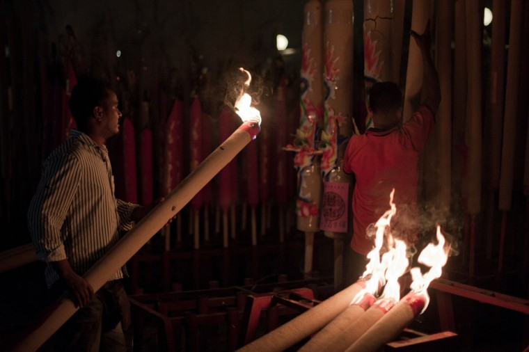 A worker carries a gigantic joss stick to welcome the Chinese New Year at a temple in Kuala Lumpur early on January 31, 2014. The Lunar New Year Year of the Horse falls on January 31 and marks the beginning of the Spring Festival holiday. (Moho Rasfan/AFP/Getty Images)
