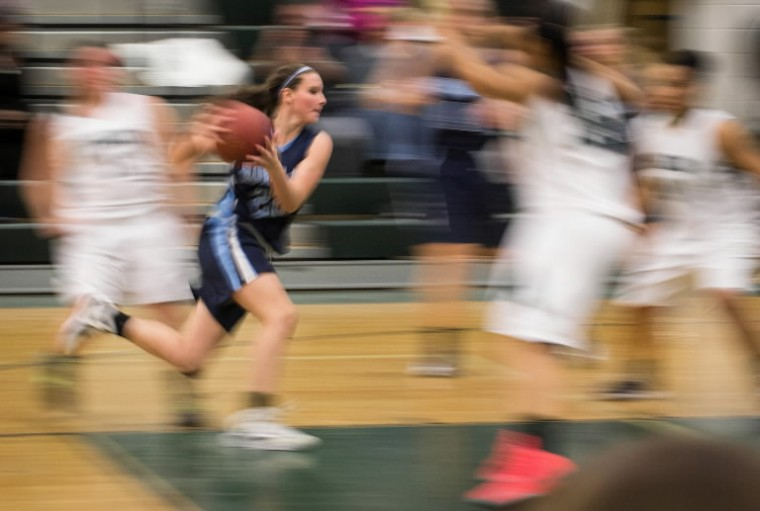 Photographer Nate Pesce slows the shutter speed to catch Howard High School's Catherine Sims rushing the ball through Atholton defenders during a girls basketball game at Atholton High School on Jan. 30. (Photo by Nate Pesce/BSMG)