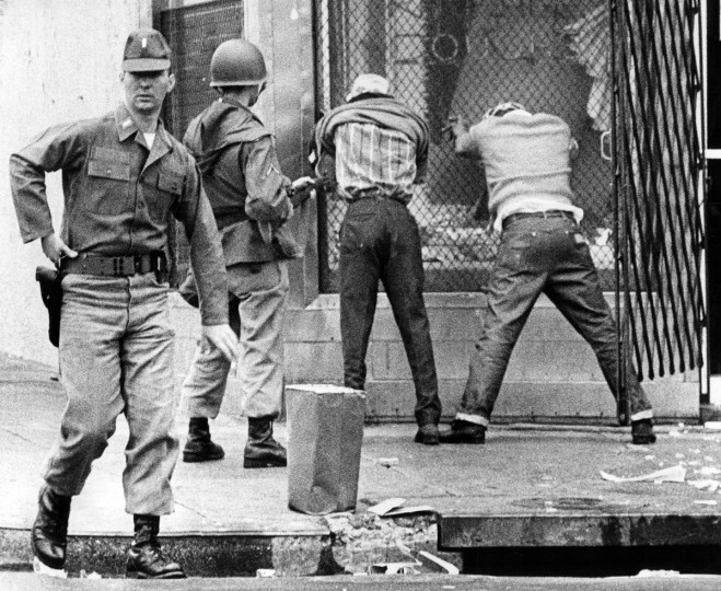 Soldiers hold two looters caught on Biddle Street near Madison during the 1968 riots that followed the killing of Dr. Martin Luther King Jr. in April. (Paul Hutchins/Baltimore Sun)