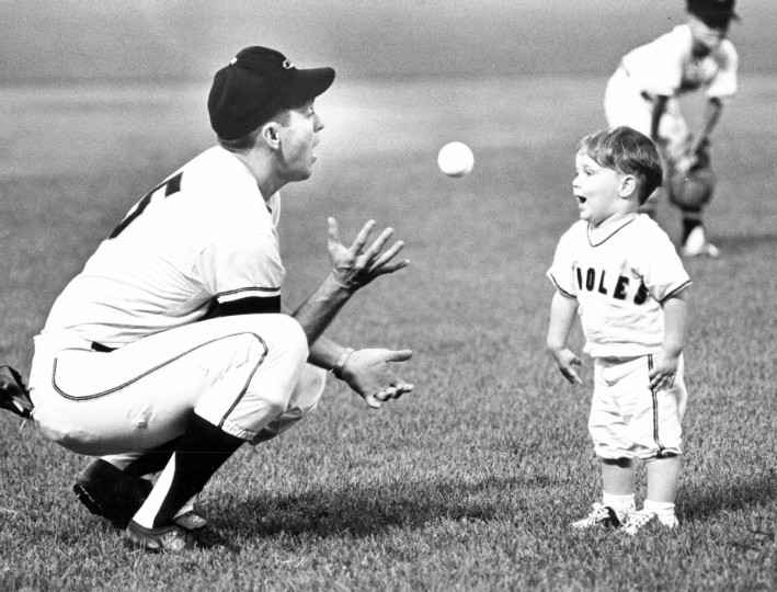 On August 22, 1965 Brooks Robinson's expression is matched by his son as they play catch at Memorial Stadium before the Orioles contest. (Paul Hutchins/Baltimore Sun)