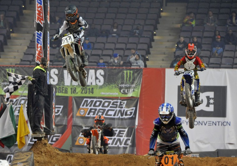 Airborne over the top hill in the Supermini 1 race are #517 Ian Kearon of Lake Hopatcong, NJ, left, and #127 Nathan Murphy of Mount Airy, MD, right, in the Baltimore Amateur AMSOIL Arenacross event at the Baltimore Arena. In foreground #01 is Hunter McClung of Joppa, MD. (Amy Davis/Baltimore Sun)