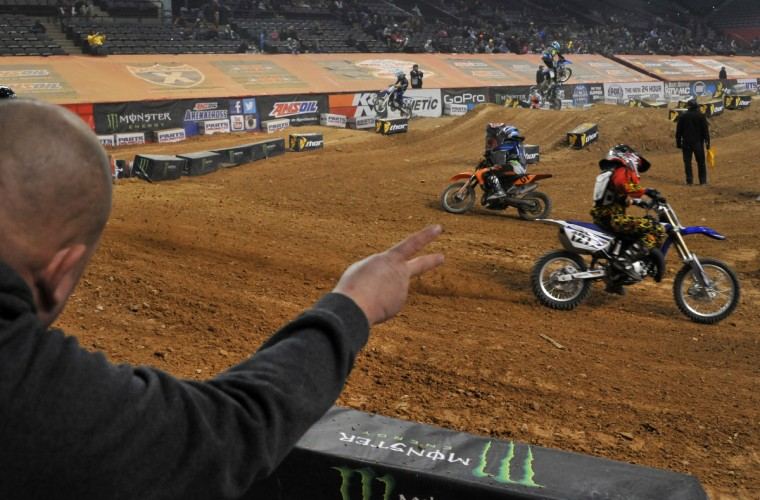 Some fathers and other supporters of competitors watch the race from the stage next to the starting gate to cheer them on during the Baltimore Amateur AMSOIL Arenacross event at the Baltimore Arena. (Amy Davis/Baltimore Sun)