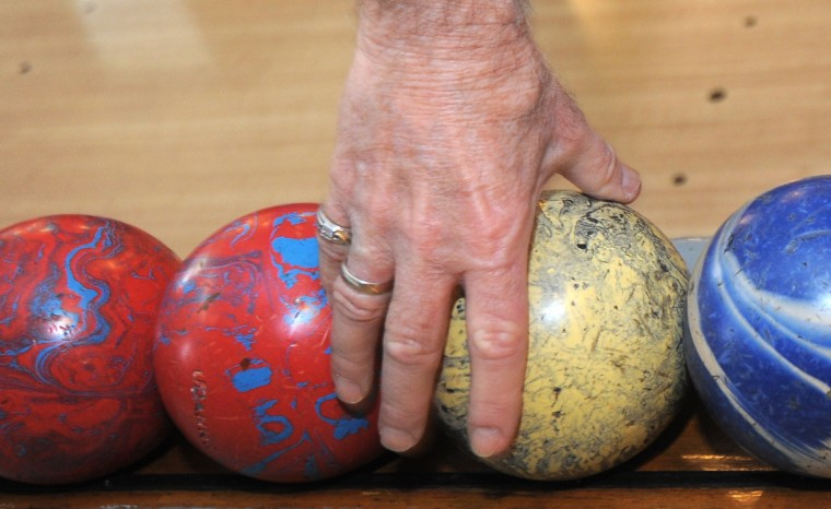 Richard Kulacki, 73, who bowls with the John Booth Senior League, reaches for a duckpin bowling ball. (Algerina Perna/Baltimore Sun)