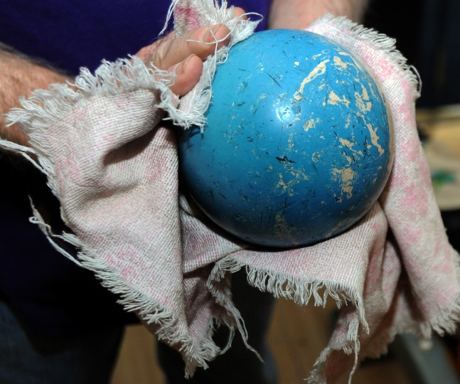 Richard Kulacki, 73, who plays in the John Booth Senior League, wipes off a duckpin bowling ball to ensure a better grasp at the Patterson Bowling Center. (Algerina Perna/Baltimore Sun)