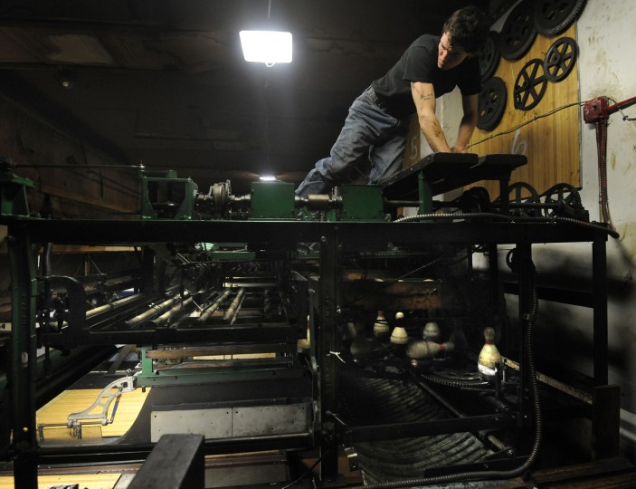 J.B., one of the pinsetters and mechanics, adjusts a Sherman machine to reset a bowling lane. (Algerina Perna/Baltimore Sun)