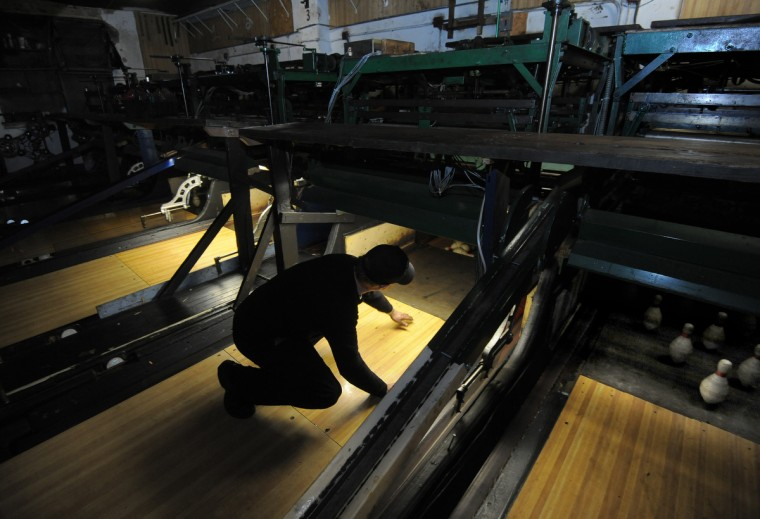 It takes both man and machine to keep bowling machines running at Patterson Bowling Center, the home of duckpin bowling center. (Algerina Perna/Baltimore Sun)
