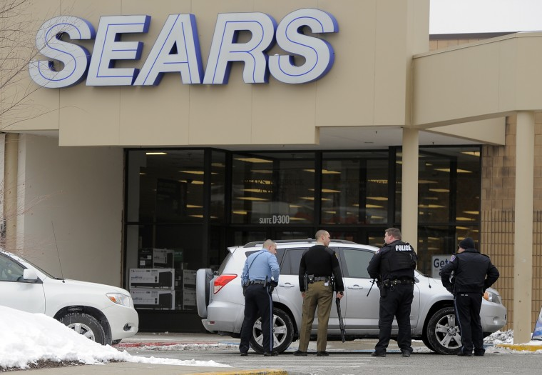 Police officers are stationed outside an entrance to Sears at The Mall in Columbia Three people are dead after a shooting Saturday morning on an upper level of the mall. (Kim Hairston/Baltimore Sun Staff).