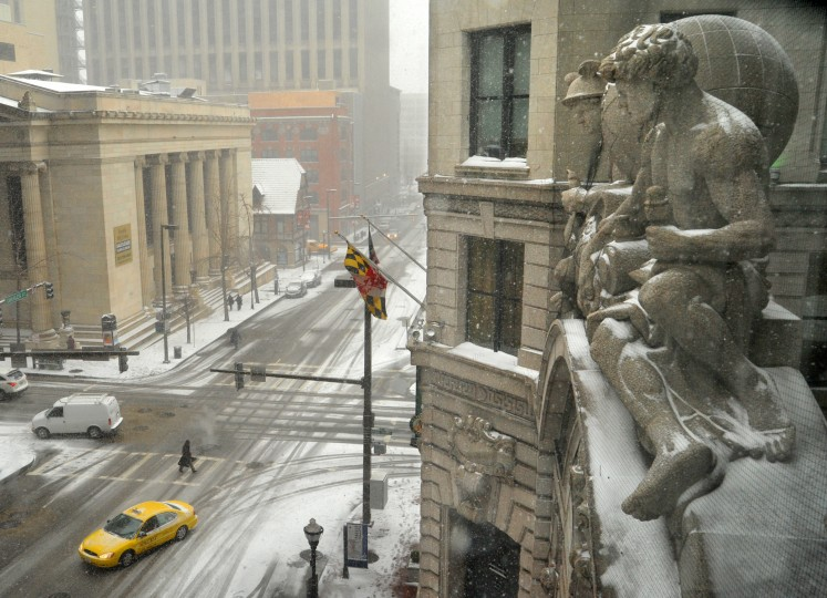 The Roman god Mercury, representing commerce, and another figure, representing the Progress of Industry, look down on the snowy scene at N. Charles and Baltimore Streets from above the entrance to the Hotel Monaco. The sculptures date back to the building's origins as the B&O Railroad headquarters. (Amy Davis / Baltimore Sun)
