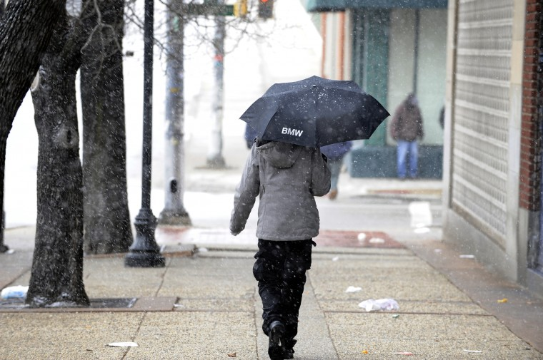 A pedestrian walks along North Avenue near Howard Street as a snow storm starts in the city. (Barbara Haddock Taylor/Baltimore Sun)