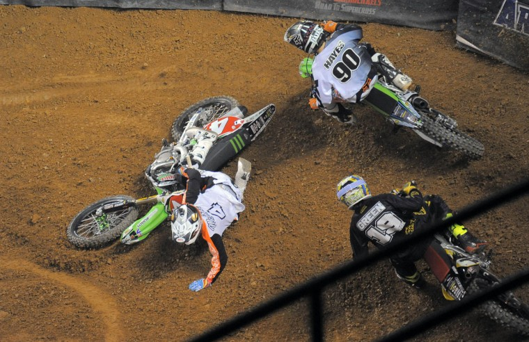 Michael McDade (4) , who was among the leaders during his heat, wipes out in front of Jacob Hayes (90) at a hairpin turn in a 15-lap AMSOIL Arenacross race, during Baltimore Arenacross at the Baltimore Arena, Jan. 11, 2014. (Karl Merton Ferron/Baltimore Sun Photo)