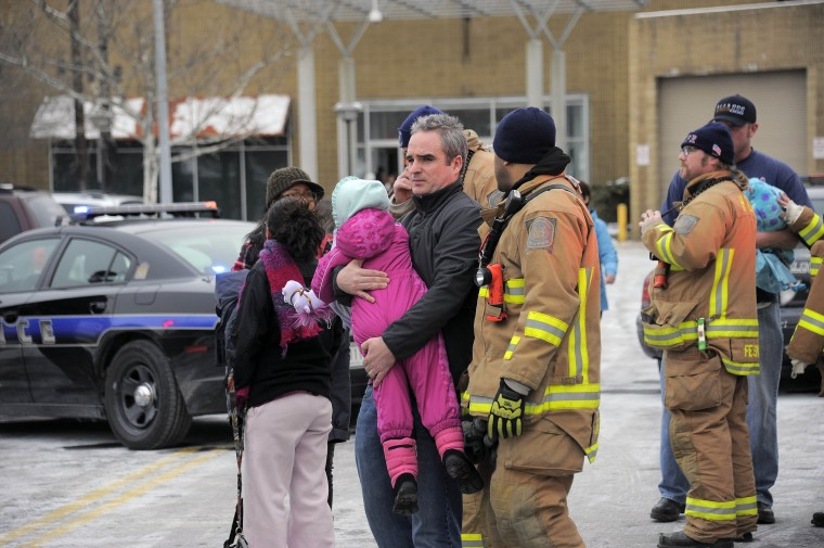 A man carries a child past rescue personnel after leaving the food court area during a shooting inside the Columbia Mall Saturday, Jan. 25, 2014. At least three people are confirmed dead, including the shooter, according to news reports claiming police as the source of the information. (Karl Merton Ferron/Baltimore Sun Staff)