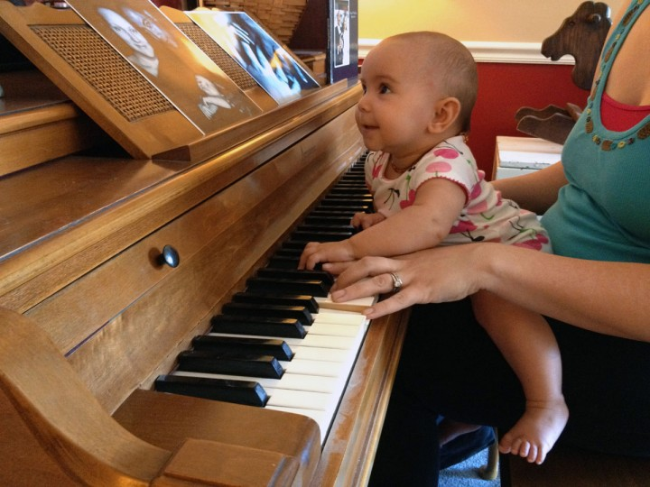 Karah Ferron sits in her mother's lap as they play the piano on June 28, 2013. (Karl Merton Ferron/Baltimore Sun Staff)