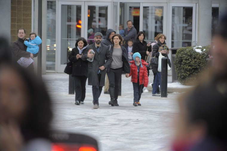 People exit the food court area during a shooting scene inside the Columbia Mall Saturday, Jan. 25, 2014. At least three people are confirmed dead, including the shooter, according to news reports claiming police as the source of the information. (Karl Merton Ferron/Baltimore Sun Staff)