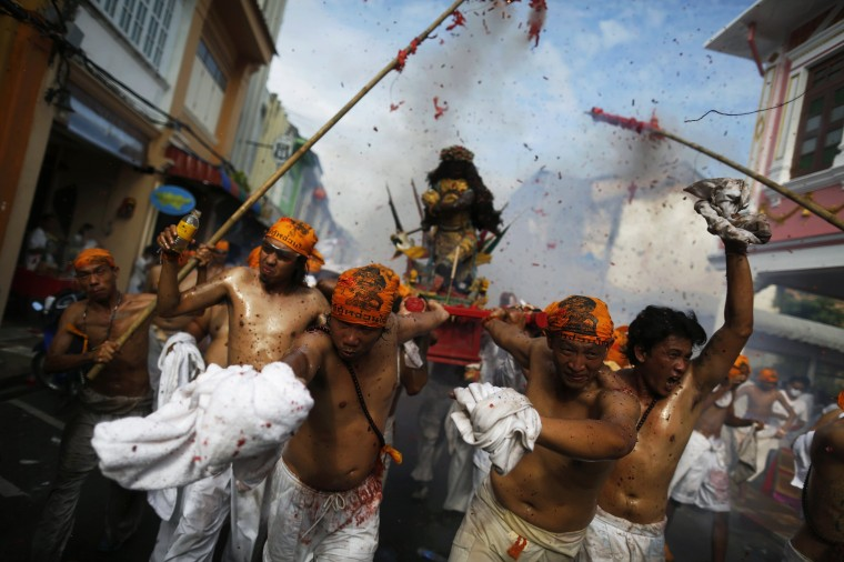 Vegetarian Festival: Devotees of the Chinese Jui Tui Shrine carry a statue through exploding firecrackers during the annual vegetarian festival procession through central Phuket October 21, 2012. The festival, featuring face-piercing, spirit mediums, and strict vegetarianism celebrates the local Chinese community's belief that abstinence from meat and various stimulants during the ninth lunar month of the Chinese calendar will help them obtain good health and peace of mind. Participants in the piercing rituals are believed to be in a trance that makes them impervious to pain. (REUTERS/Damir Sagolj)