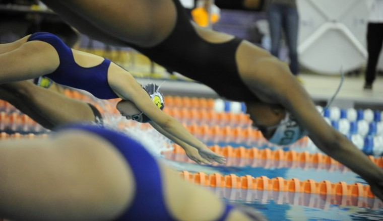 Laurel's Madison Tuttle, left, dives into the pool with the rest of the field in the 50-meter freestyle event during a swim meet at Prince George's Sports & Learning Complex in Landover on Saturday, Jan 25. (Photo by Brian Krista/BSMG)