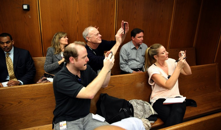 Reporters take photos of a video feed of Justin Bieber appearing in Miami misdemeanor court in Miami, Fla., on Thursday, January 23, 2014. Bieber appeared briefly in front of Judge Joseph Farina, via video, clad in red jail-issued scrubs. Bond was set at $2,500. (Walter Michot/Miami Herald/MCT)