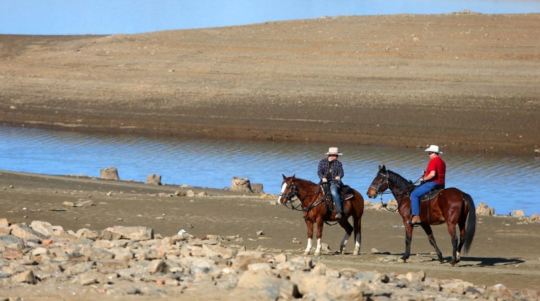 Folsom police Officers Eric Baade, left, and Daren Prociw, of the mounted enforcement detail, ride their horses across the exposed lake bed at Folsom Lake, Jan. 21, 2014, in Folsom, Calif. (Aric Crabb/MCT)