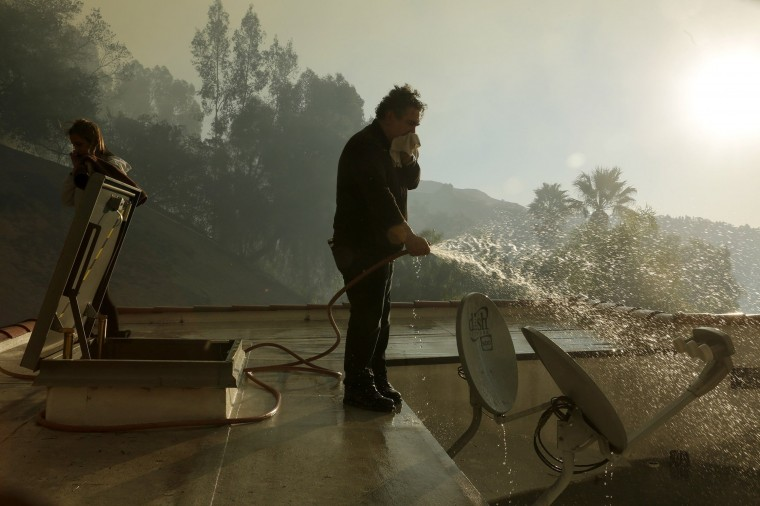 Camille Abouchedid protects his home as fire approaches his home on Kregmont Drive in Glendora, Calif., Thursday, Jan. 16, 2014. (Irfan Khan/Los Angeles Times/MCT)