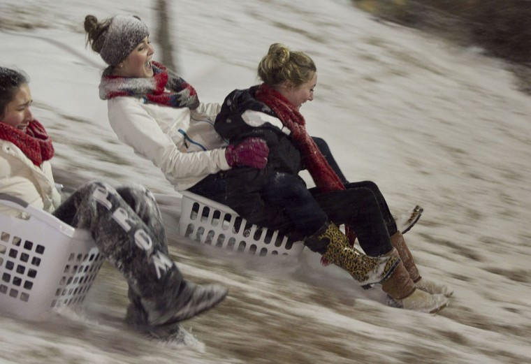 N.C. State students, from left, Gabrielle Marino, Alexa Keaney, Peyton Detwiler, use laundry baskets to hit the snowy slopes at the Court of North Carolina on the N.C. State campus in Raleigh, N.C. (Robert Willett/Raleigh News & Observer/MCT)