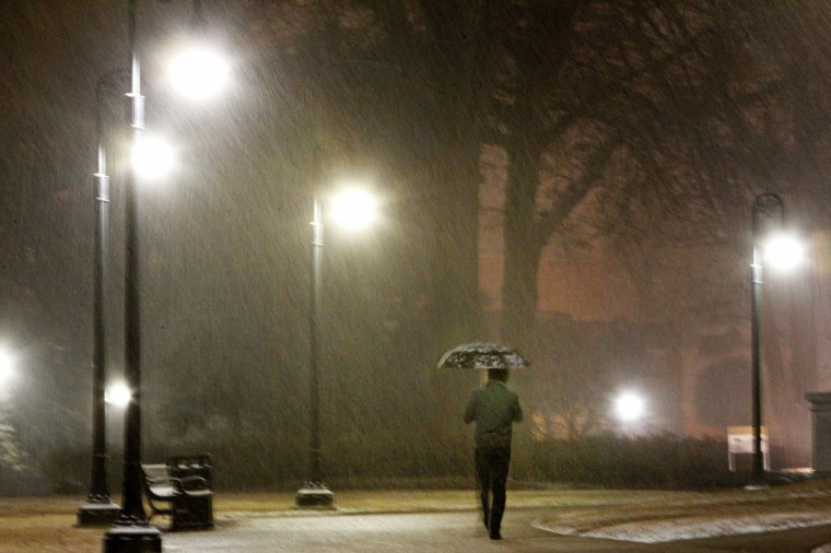 Vitor Fernandes walks the Statehouse grounds as snow falls late Tuesday evening on Jan. 28, 2014, in Columbia, S.C. (Gerry Melendez/The State/MCT)