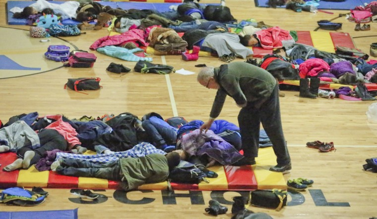 A teacher at E. Rivers Elementary School in Atlanta covers sleeping children in the gym Wednesday morning as school children were stranded overnight. (John Spink/Atlanta Journal-Constitution/MCT)