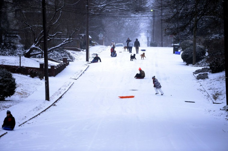 Neighbors gather on 5th Street NW in Hickory, N.C., to play in the snow. (Jeff Willhelm/Charlotte Observer/MCT)