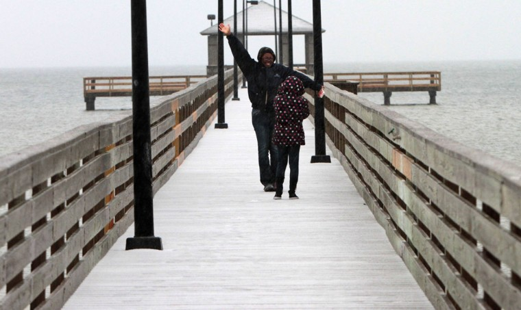 Terri White poses for a photo for her 8-year-old daughter Demilion Harris on the Lighthouse Pier in Biloxi, Miss. Frozen rain left a thin blanket of ice across South Mississippi on Tuesday. (John Fitzhugh/Biloxi Sun Herald/MCT)