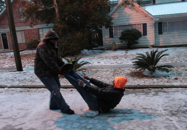 Leianna Ishler pulls Michael Kirsch down St. Paul Street in Biloxi, Miss., on an improvised sled. (John Fitzhugh/Biloxi Sun Herald/MCT)