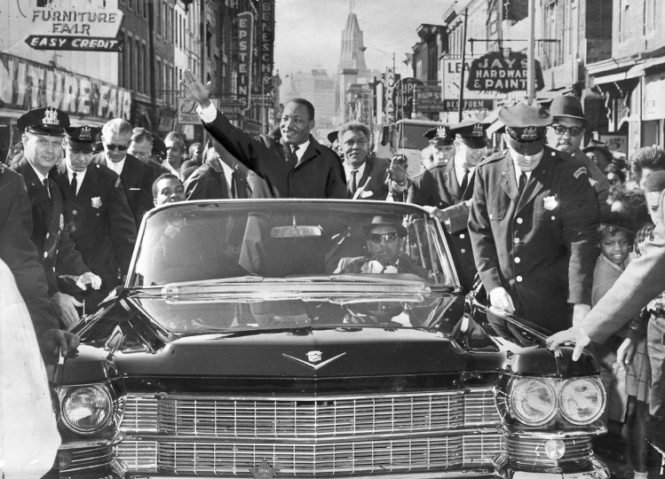 The Rev. Dr. Martin Luther King, Jr., civil rights leader and Nobel Prize winner, greets thousands of admirers on a motorcade tour up North Gay Street on October 31, 1964. (Paul Hutchins/Baltimore Sun)