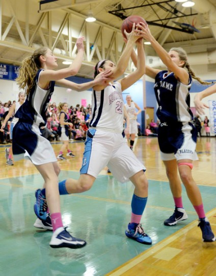 Mount de Sales' Annie Tavera, center, tries to grab a rebound, but Notre Dame Prep's Morgan Bracken, right, and Marisa DeLuca, try to interfere during the Mount de Sales Pink Out basketball game, Friday, Jan. 31, 2014, to raise money for breast cancer research. (Photo by Jon Sham/BSMG)