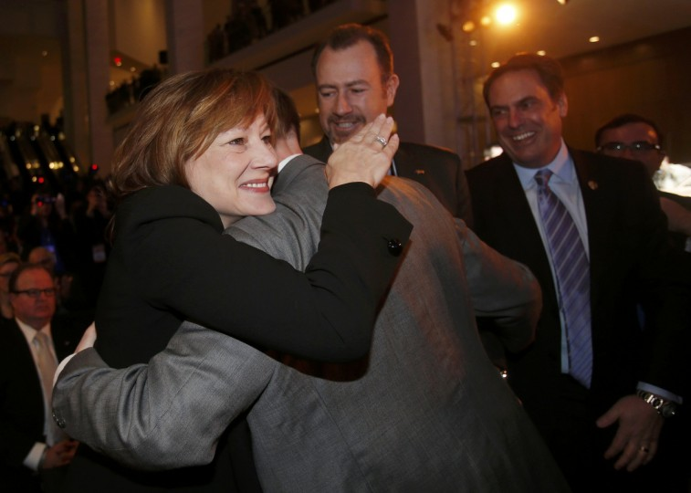 GM CEO-designate Mary Barra embraces Jeff Luke, GM Chief Engineer of full and mid-size trucks, after the Chevrolet Silverado won the Truck of the Year Award during the press preview day of the North American International Auto Show in Detroit, Michigan January 13, 2014. GM CFO Daniel Ammann (C) and President of GM North America Mark Reuss (R) look on. (Rebecca Cook/Reuters photo)