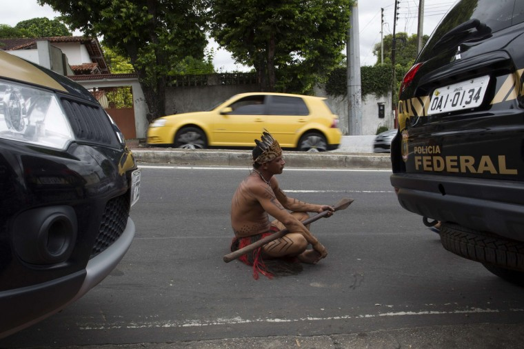 An Amazon Indian sits on the street in front of the headquarters of Brazil's Indian affairs bureau FUNAI after police expelled by court order a group of Indians who were occupying the building, in Manaus. Some 50 Indians have been occupying FUNAI's building since last November as they pressure the institution to change its current director, Eduardo Desiderio Chaves, who they complained for being a non-Indian and is accused of ignoring their needs, according to the group. (Bruno Kelly/Reuters)