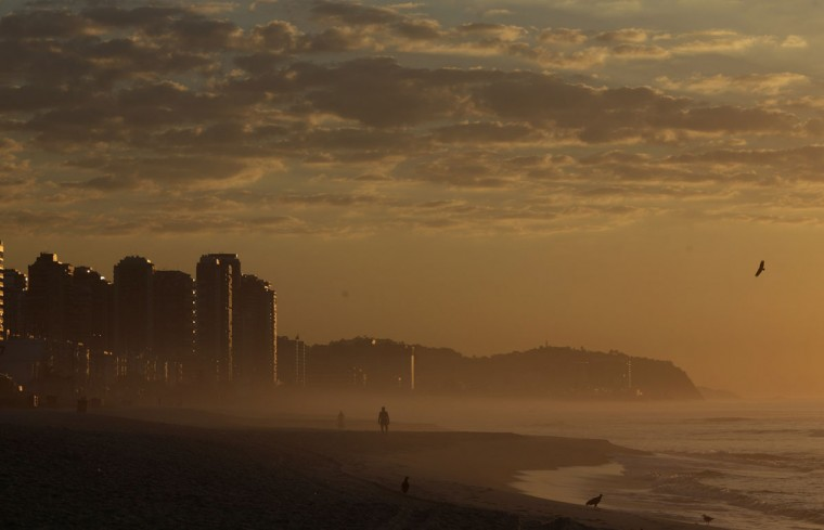 A man walks in Barra da Tijuca beach during the sunrise in Rio de Janeiro January 31, 2014. This has been the hottest January on record in parts of Brazil, and the heat plus a severe drought has fanned fears of water shortages, crop damage, and higher electricity bills that could drag down the economy during an election year for President Dilma Rousseff. (REUTERS/Ricardo Moraes)