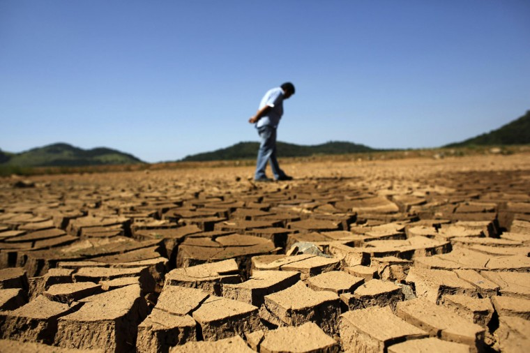 A worker of SABESP, a Brazilian enterprise of Sao Paulo state, that provides water and sewage services to residential, commercial and industrial areas looks at the cracked ground of Jaguary dam in Braganca Paulista, 100 km from Sao Paulo January 31, 2014. This has been the hottest January on record in parts of Brazil, and the heat plus a severe drought has fanned fears of water shortages, crop damage, and higher electricity bills that could drag down the economy during an election year for President Dilma Rousseff. (REUTERS/Nacho Doce)