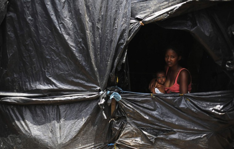"Tauana, 18, holds her three-month-old baby Kemilly Yasmin, as they pose at the window of their home, at the ""New Palestine"" camp, which houses an estimated 8,000 families of Brazil's Roofless Workers Movement, who last year occupied a 100 hectare (246 acres) plot to demand for affordable low-income housing from the government, in Sao Paulo January 9, 2014. Sao Paulo state has a deficit of 1.11 million homes, according to the Institute of Applied Economic Research. (REUTERS/Nacho Doce)"