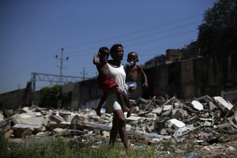 A woman carries her children as she walks past debris of a demolished area in Metro slum, near Maracana stadium, in Rio de Janeiro January 9, 2014. Residents of Metro slum are protesting against their eviction of their homes which will be demolished for the construction of a leisure and automotive trade area. The removal of the community, which is near the Maracana stadium is part of the renovation works of the area for the world cup 2014, local media said. (REUTERS/ Ricardo Moraes)