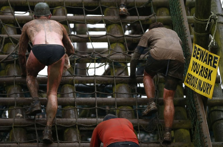 Competitors climb a cargo net during the Tough Guy event in Perton, central England, January 26, 2014. The annual event to raise cash for charity challenges thousands of international competitors in a cross country run followed by an assault course consisting of obstacles including water, fire and tunnels. (Darren Staples/Reuters)