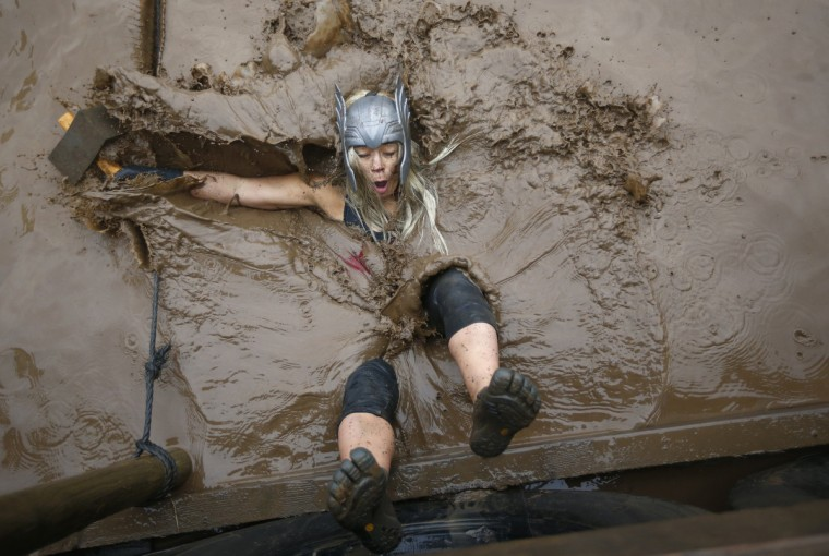 A competitor falls in to muddy water during the Tough Guy event in Perton, central England, January 26, 2014. The annual event to raise cash for charity challenges thousands of international competitors in a cross country run followed by an assault course consisting of obstacles including water, fire and tunnels. (Darren Staples/Reuters)