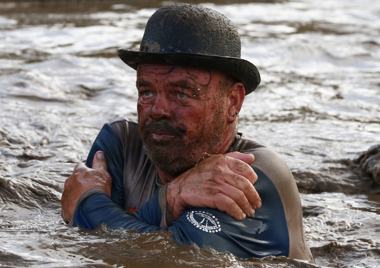 A competitor wades through muddy water during the Tough Guy event in Perton, central England, January 26, 2014. The annual event to raise cash for charity challenges thousands of international competitors in a cross country run followed by an assault course consisting of obstacles including water, fire and tunnels. (Darren Staples/Reuters)