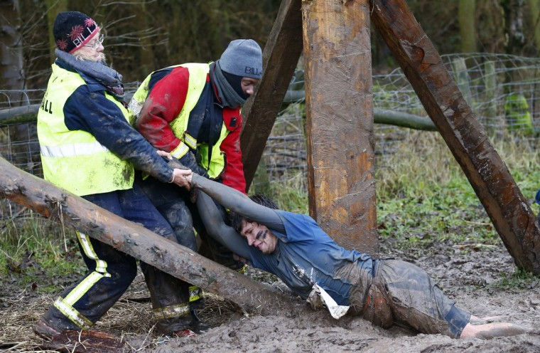 A competitor is dragged out of the mud during the Tough Guy event in Perton, central England, January 26, 2014. The annual event to raise cash for charity challenges thousands of international competitors in a cross country run followed by an assault course consisting of obstacles including water, fire and tunnels. (Darren Staples/Reuters)