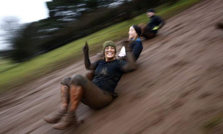 Competitors slide down a muddy bank during the Tough Guy event in Perton, central England January 26, 2014. The annual event to raise cash for charity challenges thousands of international competitors in a cross country run followed by an assault course consisting of obstacles including water, fire and tunnels. (Darren Staples/Reuters)