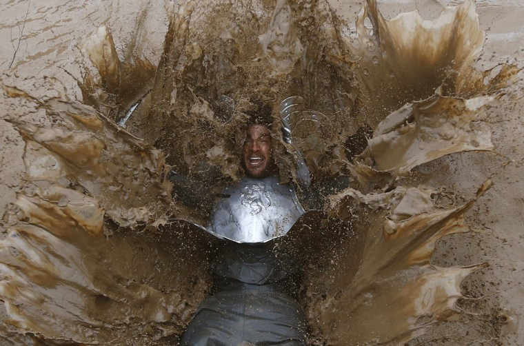 A competitor falls into muddy water during the Tough Guy event in Perton, central England, January 26, 2014. The annual event to raise cash for charity challenges thousands of international competitors in a cross country run followed by an assault course consisting of obstacles including water, fire and tunnels. (Darren Staples/Reuters)
