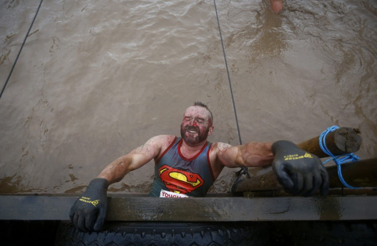 A competitor hangs above muddy water during the Tough Guy event in Perton, central England January 26, 2014. The annual event to raise cash for charity challenges thousands of international competitors in a cross country run followed by an assault course consisting of obstacles including water, fire and tunnels. (Darren Staples/Reuters)