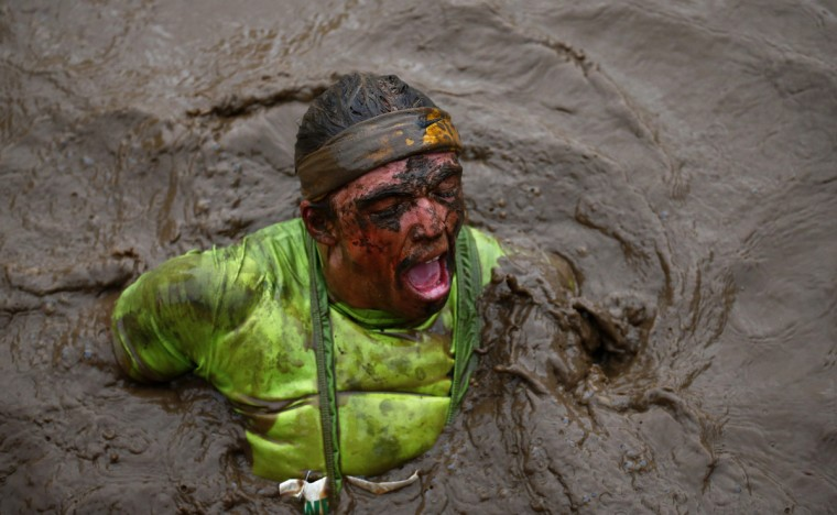 A competitor battles through muddy water during the Tough Guy event in Perton, central England January 26, 2014. The annual event to raise cash for charity challenges thousands of international competitors in a cross country run followed by an assault course consisting of obstacles including water, fire and tunnels. (Darren Staples/Reuters)